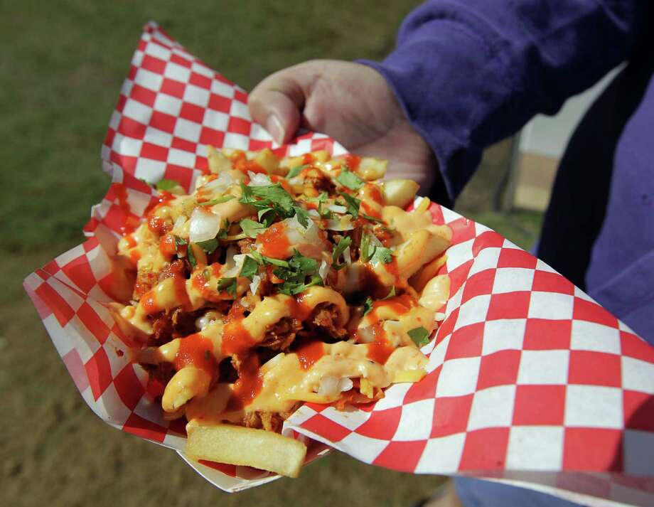 The kimchi fries with chicken from the Korean BBQ Taco truck during the Korean Festival at Discovery Green Saturday, Oct. 19, 2013, in Houston. Photo: James Nielsen, Houston Chronicle / © 2013  Houston Chronicle