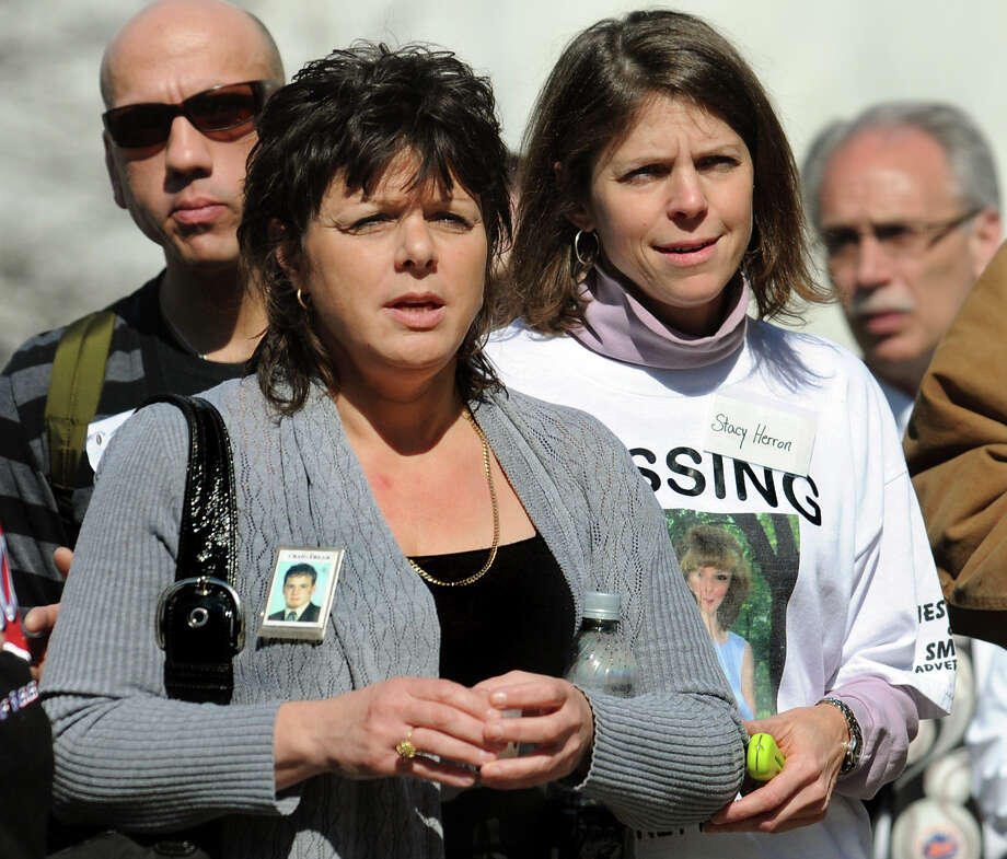 Veronica Frear, whose son Craig has been missing six years, left, and Stacy Herron, whose sister-in-law Audrey has been missing eight years, right, attend a ceremony during Missing Person's Day on Saturday, April 9, 2011, in Albany, N.Y. (Cindy Schultz / Times Union) Photo: Cindy Schultz / 00012636A