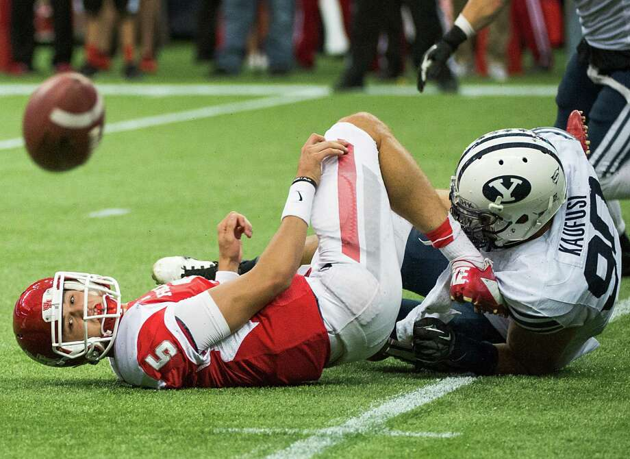 UH quarterback John O'Korn watches a lateral he made while under pressure from BYU's Bronson Kaufusi bounce away and eventually end up going out of bounds during the fourth quarter Saturday. Photo: Smiley N. Pool, Staff / © 2013  Houston Chronicle