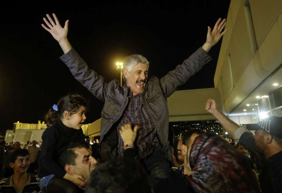 One of the nine released Lebanese Shiite pilgrims who were kidnapped by a rebel faction in northern Syria in 2012 celebrates his arrival at Rafkik Hariri International Airport in Beirut. Photo: Hussein Malla / Associated Press