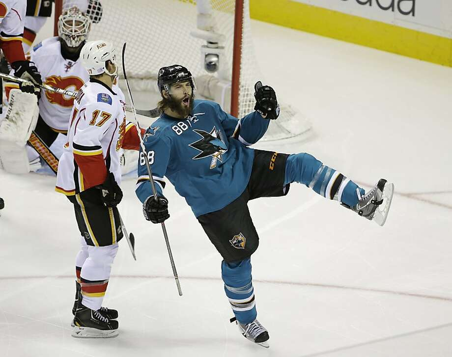 San Jose Sharks right wing Brent Burns reacts after scoring the Sharks' first goal as Calgary Flames goalie Karri Ramo, left, and Calgary Flames center Lance Bouma (17) look on during the first period of an NHL hockey game Saturday, Oct. 19, 2013, in San Jose, Calif. (AP Photo/Eric Risberg) Photo: Eric Risberg, Associated Press