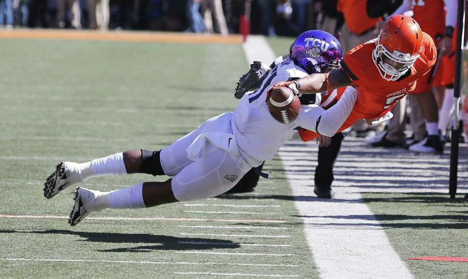 Oklahoma State wide receiver Josh Stewart reaches for a first down as he is pushed out of bounds by TCU defender Paul Dawson. Stewart had 265 all-purpose yards for the Cowboys. Photo: Sue Ogrocki / Associated Press