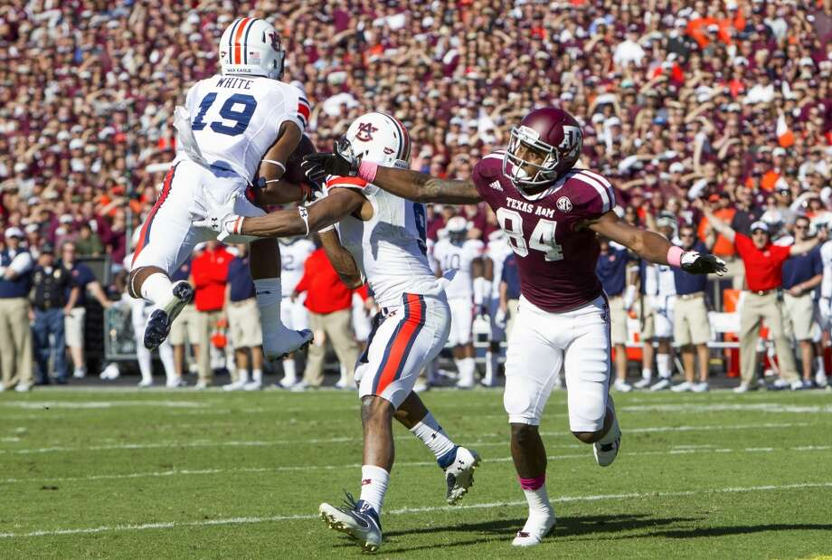 Auburn defensive back Ryan White, left, intercepts a pass intended for Texas A&M wide receiver Malcome Kennedy. Photo: Cody Duty, Houston Chronicle