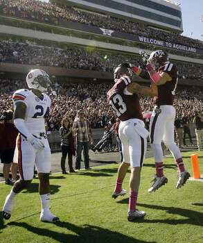Auburn defensive back Ryan Smith looks on as Texas A&M wide receivers Mike Evans, center, and Travis Labhart, right, celebrate Evans' 65-yard touchdown during the first quarter. Photo: Cody Duty, Houston Chronicle