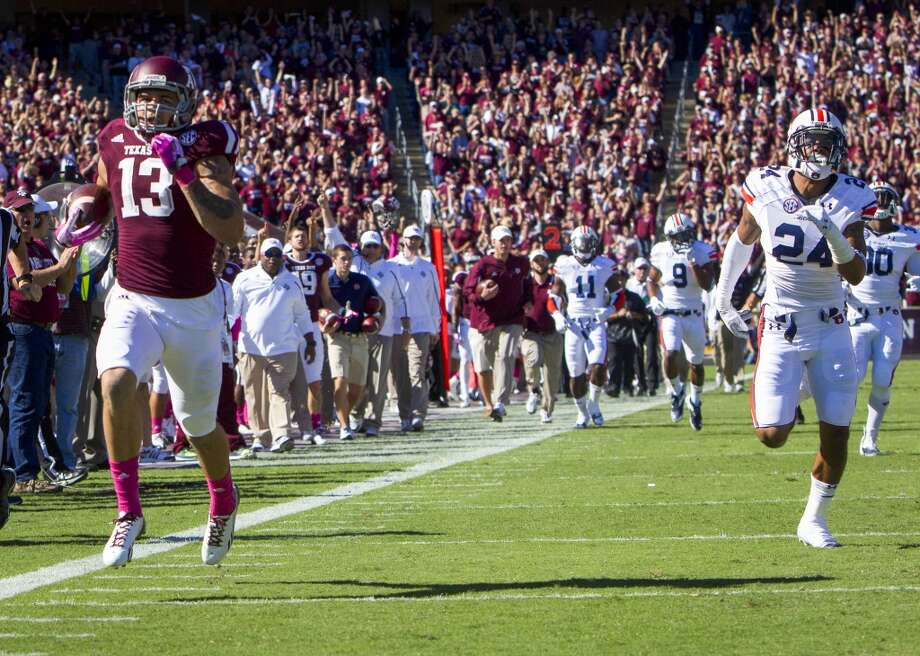 Texas A&M wide receiver Mike Evans scores on a 65-yard touchdown pass during the first quarter. Photo: Cody Duty, Houston Chronicle