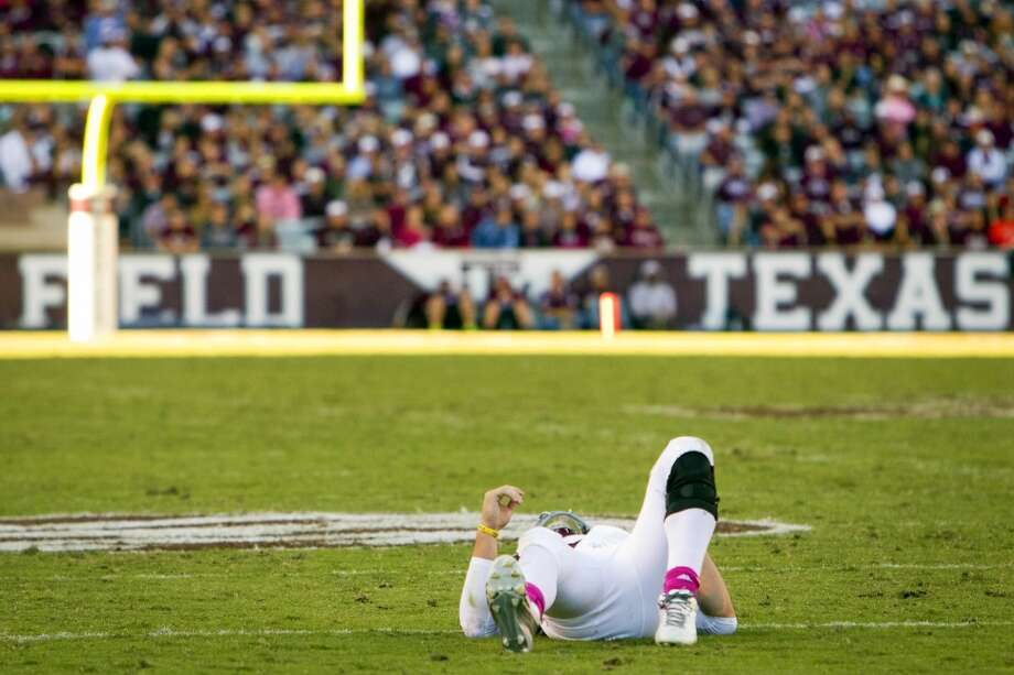 Texas A&M quarterback Johnny Manziel is slow to get after he was injured during the fourth quarter. Photo: Cody Duty, Houston Chronicle