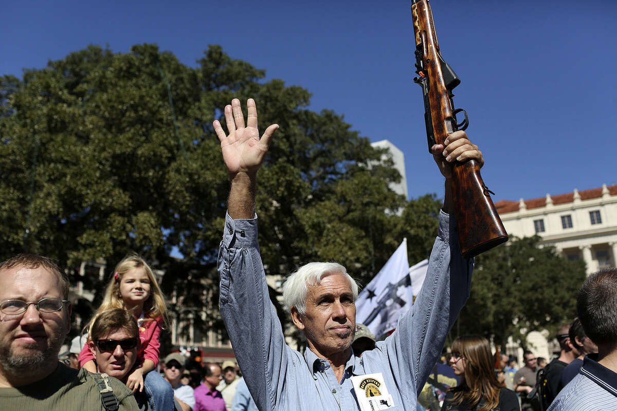 Marion Thompson of San Antonio raises a rifle in the air. Between 450 and 500 people attended the rally at the Alamo.