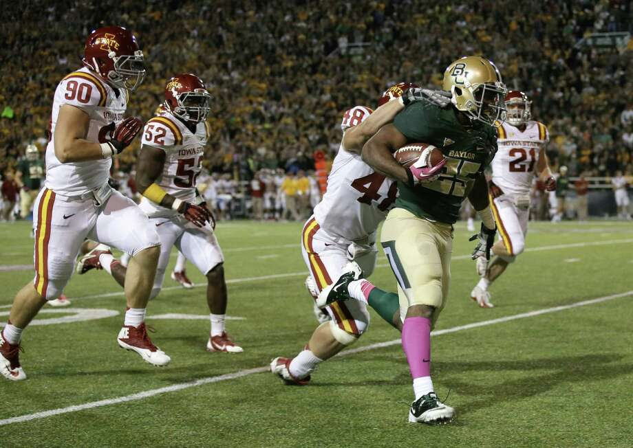 Baylor's Lache Seastrunk carries Iowa State defensive end Cory Morrissey for extra yardage in front of two other Cyclones in the first half. Seastrunk, who didn't play much in the second half, had 112 yards. Photo: Tony Gutierrez / Associated Press