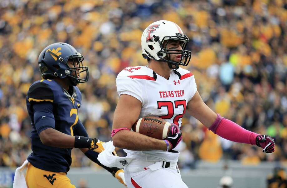 Texas Tech tight end Jace Amaro, a MacArthur-ex, scores one of his two TDs Saturday in front of West Virginia's Daryl Worley during the first quarter. Photo: Chris Jackson / Associated Press