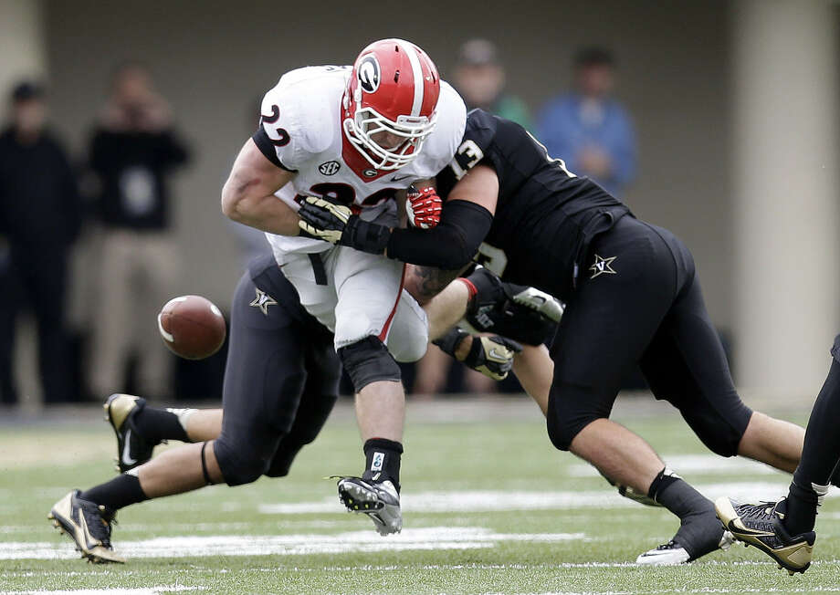 Georgia running back Brendan Douglas fumbles as he is hit by Vanderbilt linebacker Jake Sealand late in the fourth quarter of the Commodores' comeback victory over the Bulldogs in Nashville, Tenn. Photo: Mark Humphrey / Associated Press