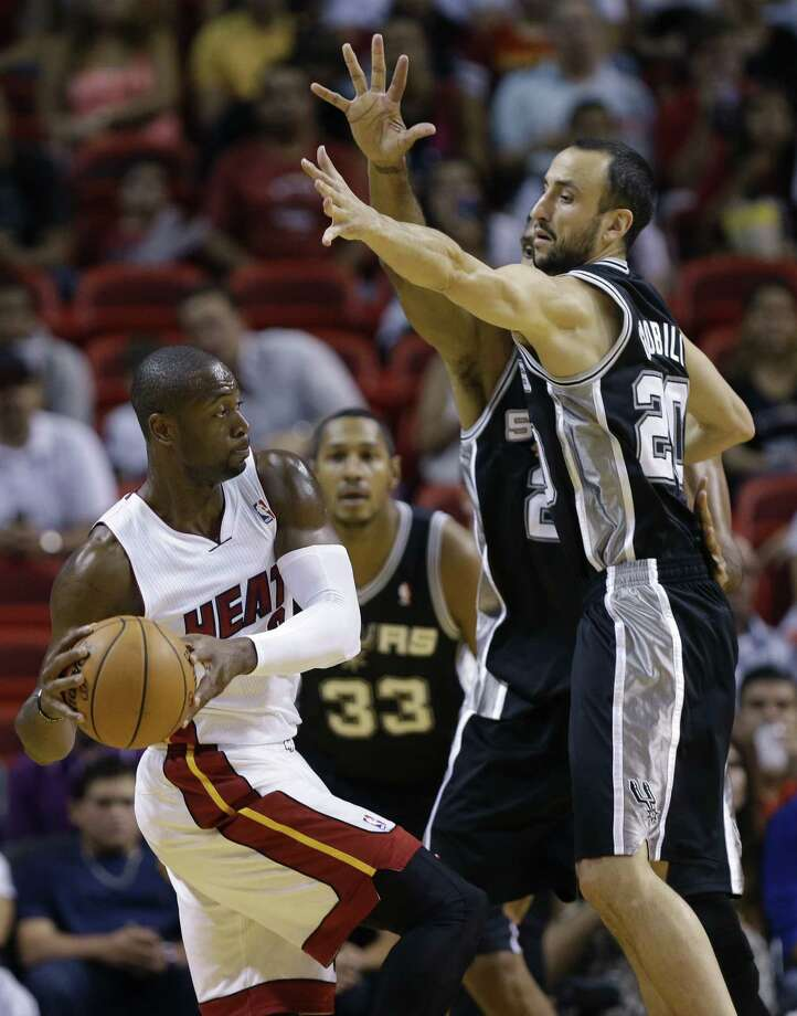Dwyane Wade (left), who led all players with 25 points, is guarded by Kawhi Leonard and Manu Ginobili (right). Photo: Lynne Sladky / Associated Press