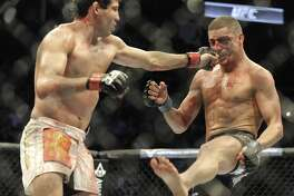 Gilbert Melendez, left, delivers a punch to Diego Sanchez in a UFC lightweight bout in Houston, Saturday, Oct. 19, 2013. Melendez won on a unanimous decision. (AP Photo/Pat Sullivan)