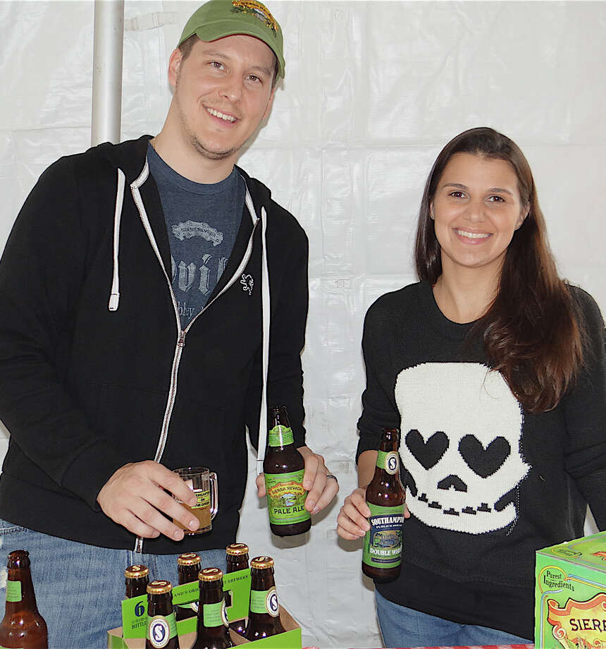 Michael Ward samples Sierra Nevada Pale Ale while his wife Nicole pours Southhampton Double White at the 2nd annual Biergarten on the Green event held Saturday. Photo: Mike Lauterborn / Westport News contributed