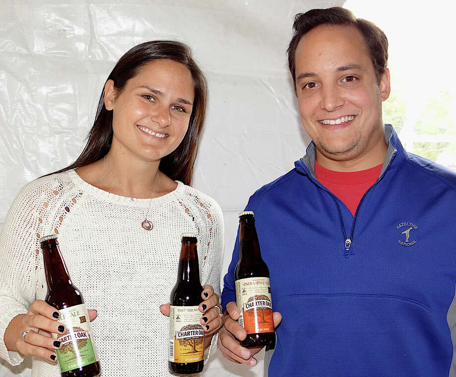 Kristen and Carlos Martinez pour samples of Charter Oak Brewing brands at Saturday's Biergarten on the Green. Photo: Mike Lauterborn / Westport News contributed