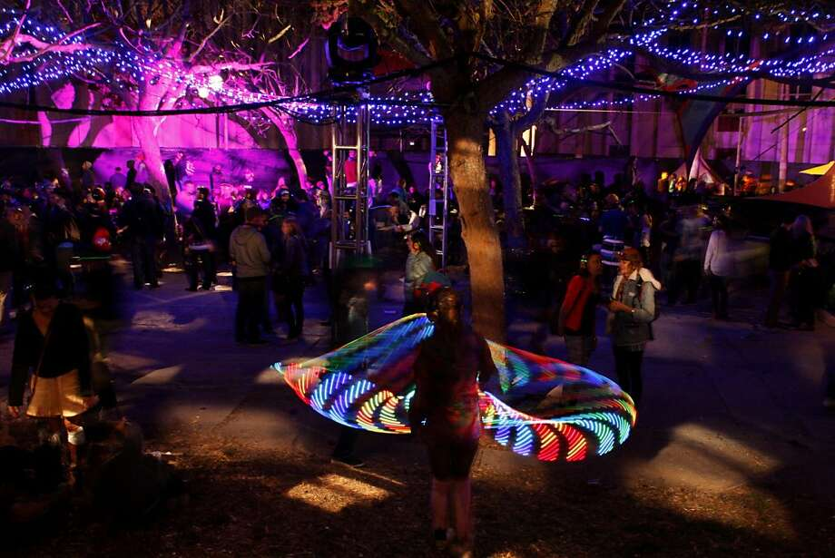 Chelsea Wright spins her LED hoop in the foreground at the Silent Frisco area where the crowd listens to a DJ through only wireless headphones at the Treasure Island Music Festival in San Francisco, Calif. on Saturday, Oct. 19, 2013. Photo: Raphael Kluzniok, The Chronicle