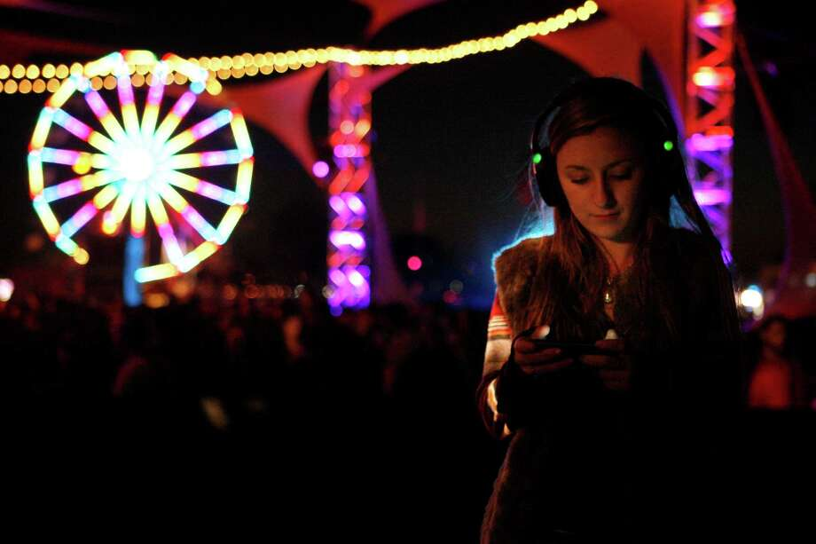 Allison Miller of San Francisco listens through wireless headphones while she checks her phone at the Silent Frisco area at the Treasure Island Music Festival in San Francisco, Calif. on Saturday, Oct. 19, 2013. Photo: Raphael Kluzniok / The Chronicle / ONLINE_YES