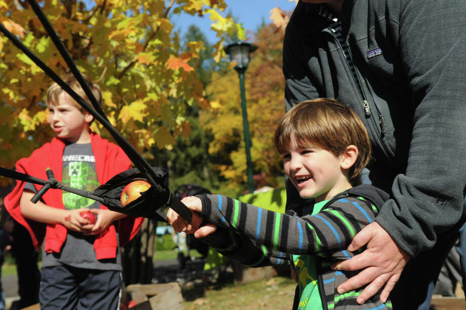 Jason O'Brien, 5, prepares to launch and apple as his brother Nicholas, 8, left, looks on at the Stamford Museum and Nature Center's Annual Harvest Festival Weekend in Stamford, Conn., Oct. 20, 2013. Photo: Keelin Daly / Stamford Advocate Freelance