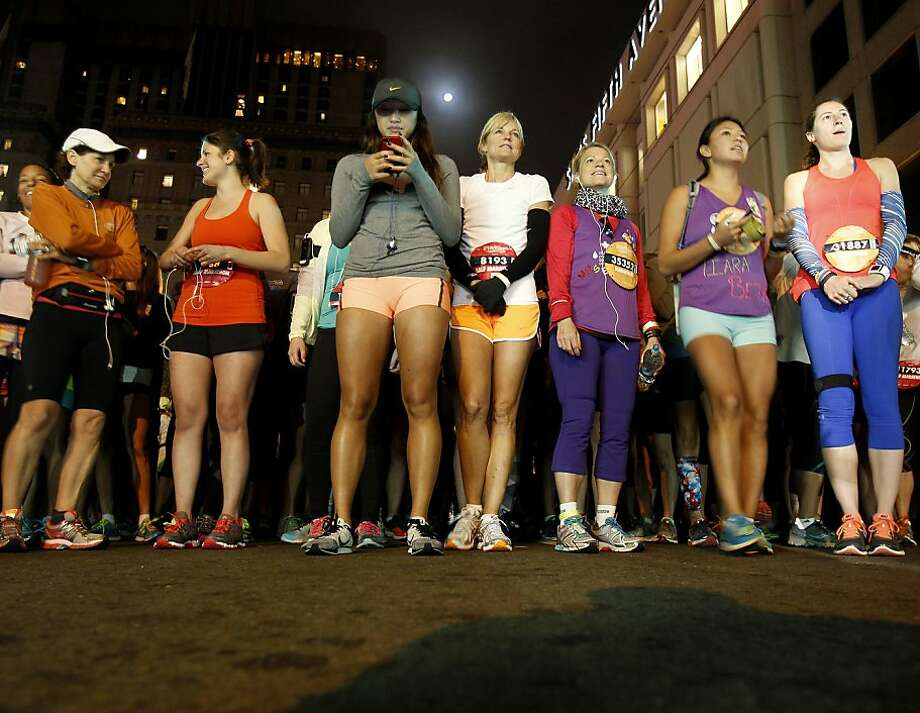 Runners on Post Street waited for the race to begin as the moon rose behind them Sunday October 20, 2013 in San Francisco, Calif. Thousands of women and a few men took part in the annual Nike Women's Marathon which began at Union Square and finished along the Great Highway. Photo: Brant Ward, The Chronicle