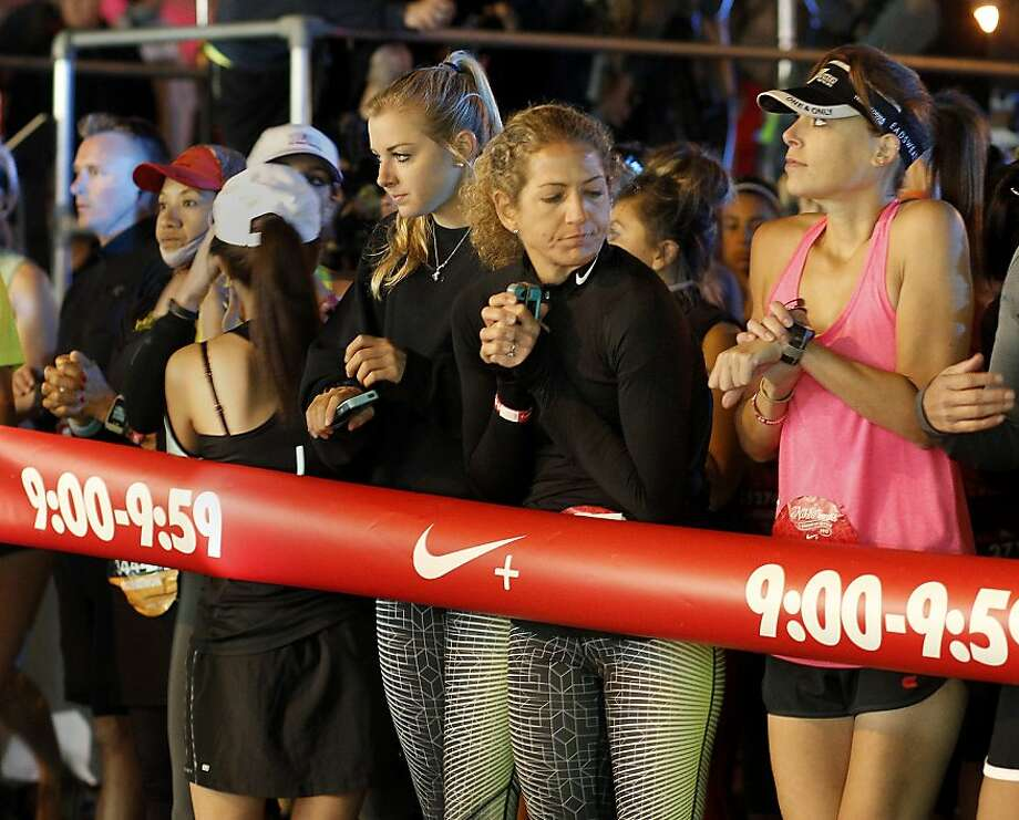 Women near the start of the second wave tried to stay warm Sunday October 20, 2013 in San Francisco, Calif. Thousands of women and a few men took part in the annual Nike Women's Marathon which began at Union Square and finished along the Great Highway. Photo: Brant Ward, The Chronicle