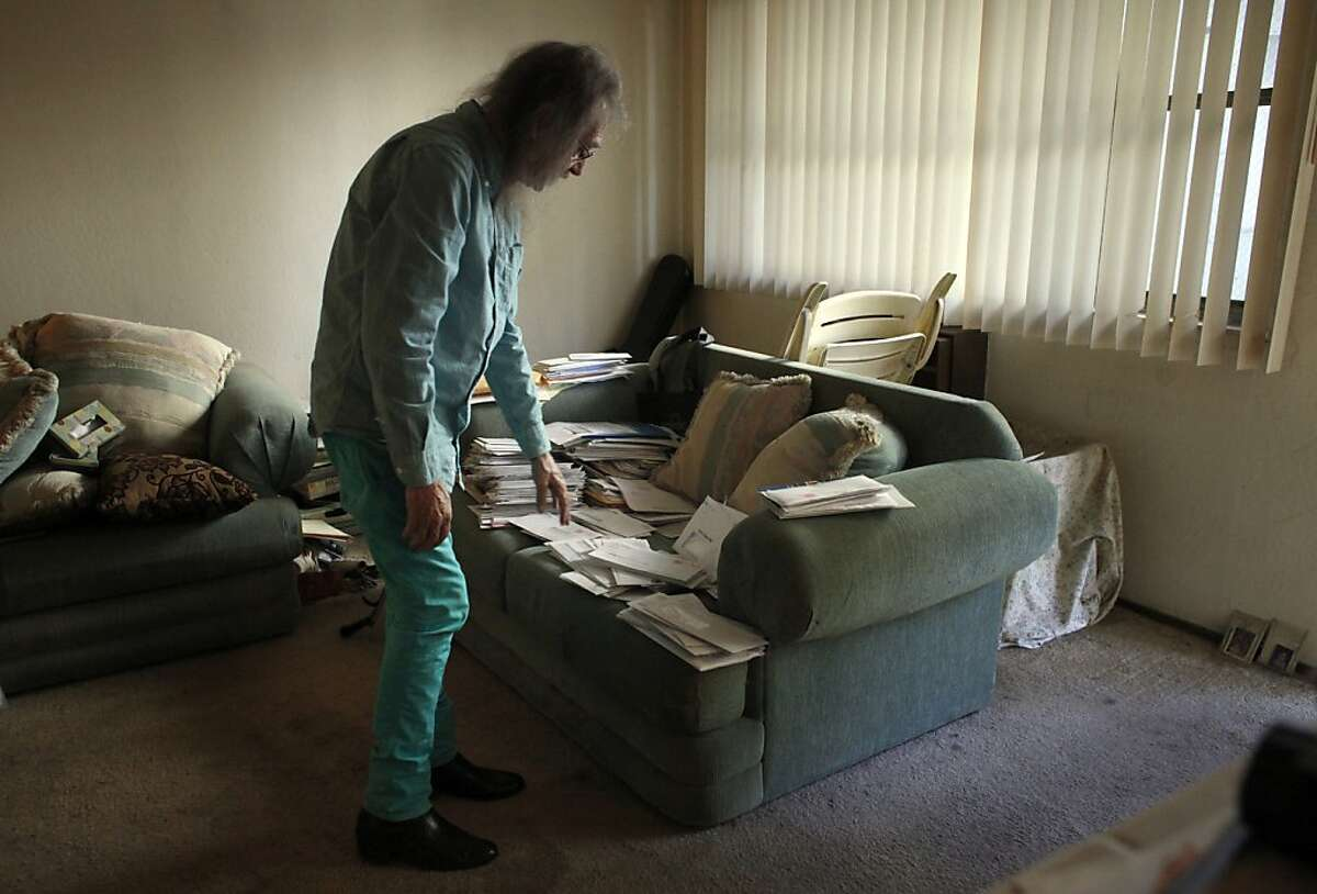 Ken McCraney, 62, looks over his medical bills at his apartment, Thursday October 3, 2013, in San Jose, Calif.