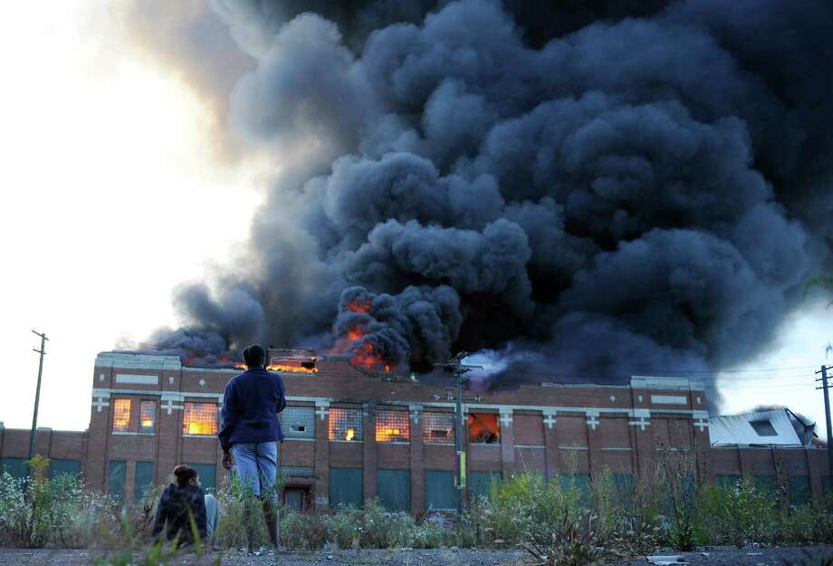 In this Sept. 26, 2013 file photo, onlookers watch as a large plume of smoke rises above a warehouse building on Detroit's west side. Some people who work near the site of a big warehouse fire last month say they have been experiencing health problems, including trouble breathing, since the blaze. (AP Photo/Detroit News, Elizabeth Conley)  Photo: Elizabeth Conley, AP / Detroit News