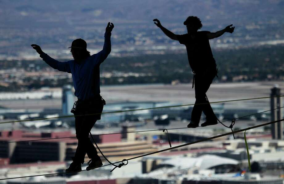 With McCarran Airport in the background, daredevil slackline athletes Mickey Wilson, left, and Andy Lewis participate in a urban highline walk outside the 63rd floor of the Mandalay Bay in Las Vegas on Oct. 16 , 2013. (AP Photo/Las Vegas Review-Journal, Jason Bean) Photo: JASON BEAN, AP / ©JASON BEAN/LAS VEGAS REVIEW-JOURNAL2013