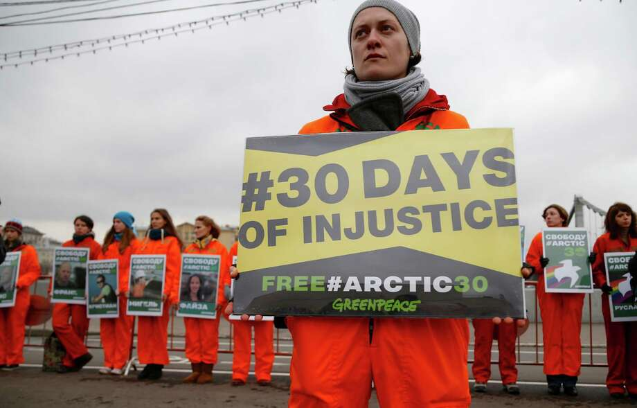Russian Greenpeace activists display photos of arrested  Greenpeace members during a protest in Moscow, Russia, Friday, Oct. 18, 2013. The group demanded the release of Greenpeace activists and journalists detained in Russia on piracy charges as they held a protest at a Russian oil platform in the Arctic. Photo: Alexander Zemlianichenko, AP / AP