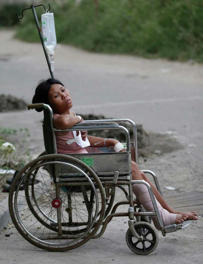 An earthquake victim sits on a wheelchair outside a government hospital following a 7.2-magnitude quake that hit Cebu city in central Philippines Tuesday, Oct. 15, 2013. The tremor collapsed buildings, cracked roads and toppled the bell tower of the Philippines' oldest church Tuesday morning, causing multiple deaths across the central region and sending terrified residents into deadly stampedes. Photo: Bullit Marquez, AP / AP2013