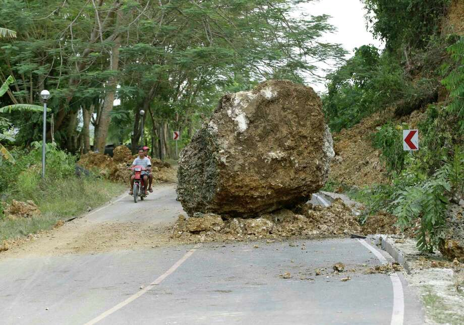 A huge boulder sits in the middle of a highway at Cortes township, Bohol province in central Philippines Wednesday Oct. 16, 2013, a day after a 7.2-magnitude quake hit Bohol and Cebu provinces. The tremor collapsed buildings and cracked roads on Tuesday morning, causing multiple deaths across the central region. Photo: Bullit Marquez, AP / AP2013
