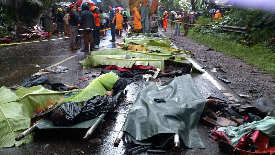 Bodies of the victims in a road accident lie on the highway at Atimonan township, Quezon province, about 115 kilometers (72 miles) southeast of Manila, Philippines Saturday Oct. 19, 2013.  A truck carrying hog feed smashed into the rear of a passenger bus on a remote downhill provincial road in the Philippines early Saturday, setting off a series of wrecks that left at least 20 people dead and injured 44 others, police said. The bus driver lost control of his vehicle after the first collision and hit two buses and four vans coming from the opposite direction before toppling over on the narrow downhill road in Quezon province, police chief Jonar Yupio said. Photo: Uncredited, AP / AP2013