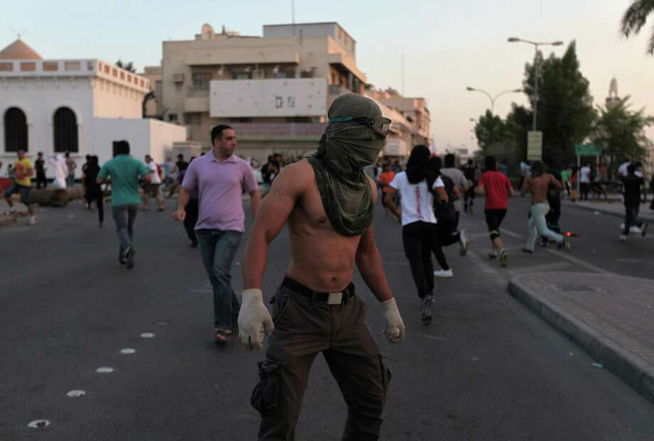 Bahraini anti-government protesters confront riot police during clashes in Musalla, Bahrain, Tuesday, Oct. 15, 2013. Clashes broke out after a traditional third-day procession for a politically active youth, Yousef al-Nashmi, a Bahraini prisoner who died after transferred to a hospital. Photo: Hasan Jamali, AP / AP