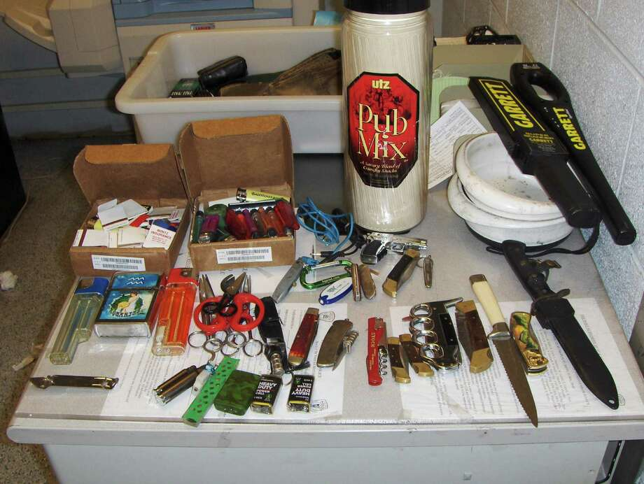 In this photo provided by the Police Department of the Port Authority of New York and New Jersey, a collection of large knives, cigarette lighters, scissors and matches fill a table at the Port Authority Police facility located in the John F. Kennedy International Airport in the Brooklyn Borough of New York, Saturday, Oct. 19, 2013. The items were sized after an airport baggage screener noticed the items in a person's carry-on bag. The Port Authority Police arrested Timothy Schiavo, Jr., 29, Patchogue NY and charged him with criminal possession of a weapon. Photo: AP / Port Authority of NY and NJ Police Dept.