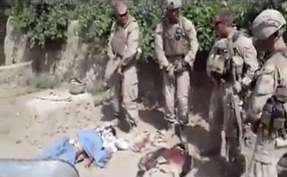 "This file image made from undated video posted on the Internet on Wednesday, Jan. 11, 2012 by a YouTube user who identified themself as ""semperfiLoneVoice"" shows men in U.S. Marine combat gear, standing in a semi-circle over three bodies. A U.S. Marine Corps panel is recommending that an officer be forcibly discharged for failing to supervise a group of snipers who posed for a video while urinating on dead Taliban fighters in Afghanistan. The panel of three colonels issued its ruling Thursday, Oct. 17, 2013, against Capt. James V. Clement after a three-day hearing at Marine Corps Base Quantico. Photo: Anonymous, AP / Internet"