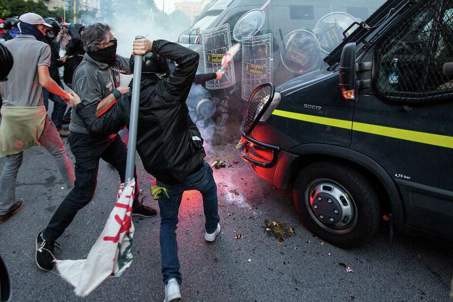 Demonstrators clash with police in Rome, Saturday, Oct. 19, 2013. Anti-austerity protesters in Rome threw eggs and firecrackers at the Finance Ministry during a march against cuts to welfare programs and a shortage in low-income housing. More than 4,000 riot police were dispatched to maintain order as tens of thousands of protesters marched through the capital on Saturday. There were moments of tension when demonstrators passed near the headquarters of an extreme-right group, but police intervened when a few bottles were thrown. Photo: Roberto Monaldo, AP / PRESL