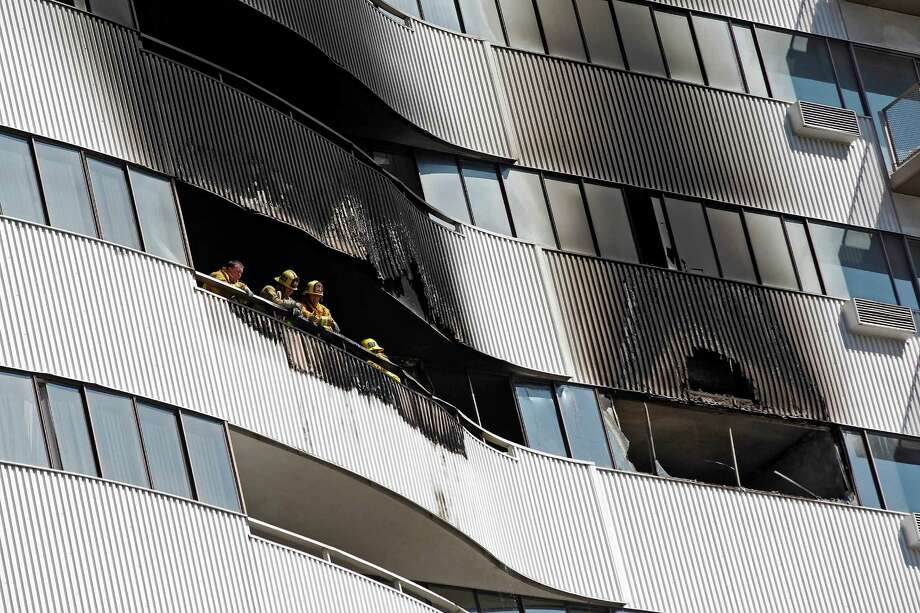 Los Angeles firefighters peer from a fire-damaged high rise apartment building on Friday, Oct. 18, 2013, in Los Angeles. Fire Department spokesman Brian Humphrey said three people were taken to hospitals and others were being assessed for non-life threatening injuries. Photo: Nick Ut, AP / AP