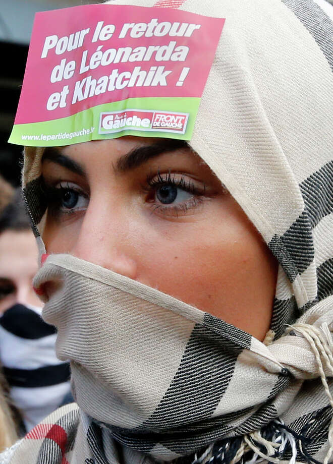 "A protesting student from a Paris high school wears a sticker reading ""For the return of Leonarda and Khatchik""  during a demonstration in Paris, Thursday, Oct. 17, 2013 in anger over expulsion of immigrant families. Kosovan girl Leonarda Dibrani was finishing up a field trip when French police showed up at the bus, detaining the 15-year-old schoolgirl in front of her classmates before authorities expelled her to Kosovo because her family's asylum application had been rejected. Khatchik refers to a recently expelled Armenian boy. Photo: Francois Mori, AP / AP"