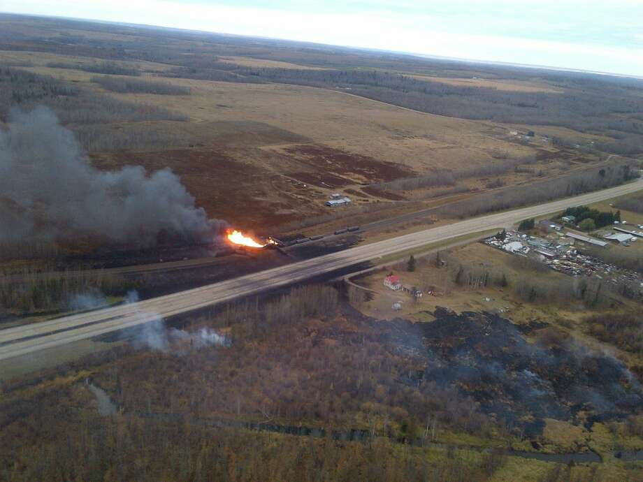 This photo provided by Royal Canadian Mounted Police, emergency crews work a massive fire after a CN tanker train carrying oil and gas derailed in Gainford, Alberta, Canada, west of Edmonton on Saturday, Oct. 19, 2013.  Canadian National spokesman Louis-Antoine Paquin said 13 cars, four carrying petroleum crude oil and nine loaded with liquified petroleum gas, came off the tracks around 1 a.m. local time in the hamlet of Gainford, about 50 miles (80 kilometers) from Edmonton. The entire community of roughly 100 people was evacuated. Photo: Uncredited, AP / AP2013