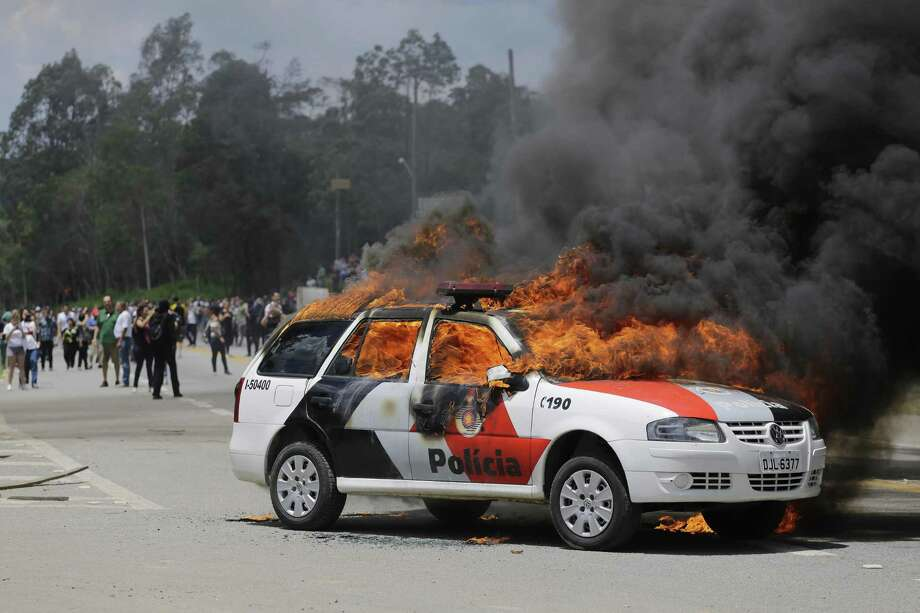 A police car burns after it was set on fire by demonstrators protesting drug testing on animals at the Instituto Royal laboratory in Sao Roque, Brazil, Saturday, Oct. 19, 2013. Clashes between animal rights activists and police outside the lab came one day after activists broke into the lab and released beagle dogs being used to test for adverse effects of drugs manufactured by the pharmaceutical industry. Protesters returned Saturday to see if there were more animals in the building. Photo: Nelson Antoine, AP / AP2013