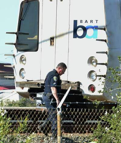 A BART police officer looks along the outside of a BART car that struck and killed two people along Jones Road in Walnut Creek, Calif., on Saturday, Oct. 19, 2013. Photo: DAN ROSENSTRAUCH, AP / - The Mercury News