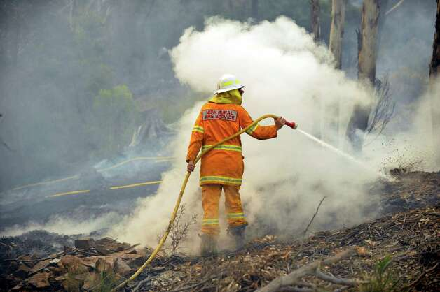 A New South Wales Rural Fire Service volunteer puts out a spot fire in the town of Bell, Australia, on Sunday, Oct. 20, 2013. Firefighters battling some of the most destructive wildfires to ever strike Australia's most populous state were focusing on a major blaze Sunday. Authorities warned that high temperatures and winds were likely to maintain heightened fire danger for days. (AP Photo/AAP Image/Paul Miller)  Photo: Paul Miller, AP / AAP Image