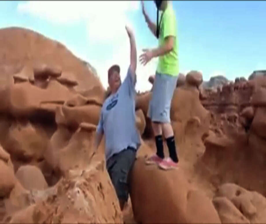 This frame grab from a video taken by Dave Hall shows  two men cheering after a Boy Scouts leader knocked over an ancient Utah desert rock formation at Goblin Valley State Park. Authorities are mulling whether to press charges against the scout leader and against the two men who cheered him on after they posted video of the incident online. The two leaders also said they have been receiving death threats for their actions (see story below). Photo: Dave Hall, AP / AP2013