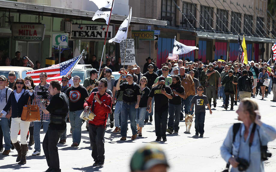 "Gun rights activists march toward Travis Park as part of the ""Come And Take It San Antonio"" rally on Saturday, Oct. 19, 2013. The event was intended to draw attention to a right Texans already have - to carry long arms publicly so long as they don't do it in a menacing manner. Photo: Kin Man Hui, AP / San Antonio Express-News"