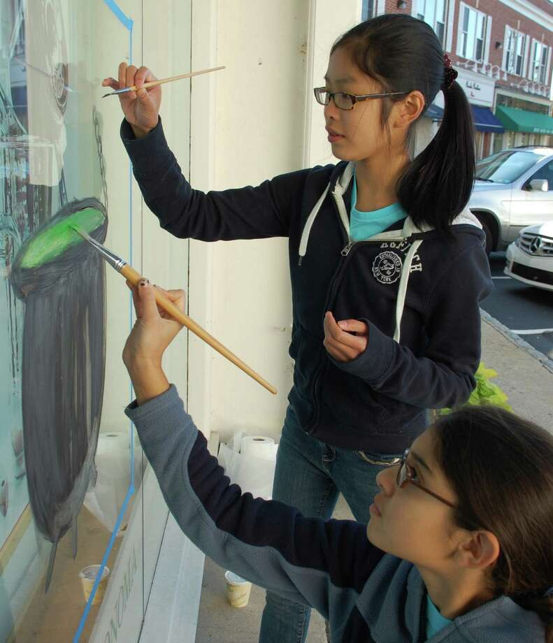 Lauren Seto, 12, left, and Nina Barandiaran, 12, both of Westport, took part in Sunday's Halloween Window Painting Contest, decorating the Williams-Sonoma store's window with a cauldron. Photo: Jarret Liotta / Westport News contributed