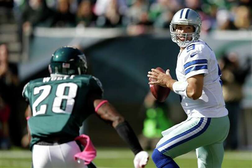 Dallas Cowboys quarterback Tony Romo, right, looks to pass as Philadelphia Eagles free safety Earl W