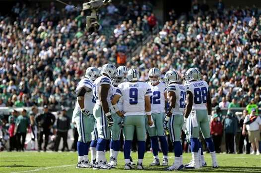 Dallas Cowboys quarterback Tony Romo (9) huddles with teammates during the first half of an NFL football game against the Philadelphia Eagles, Sunday, Oct. 20, 2013, in Philadelphia. Photo: Matt Rourke, AP / AP