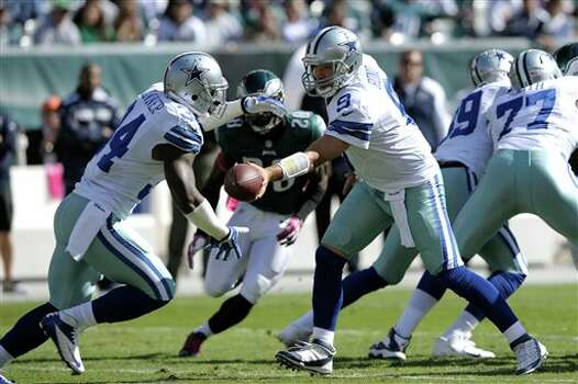 Dallas Cowboys quarterback Tony Romo (9) hands off to running back Phillip Tanner (34) during the first half of an NFL football game against the Philadelphia Eagles, Sunday, Oct. 20, 2013, in Philadelphia. Photo: Michael Perez, AP / FR168006 AP