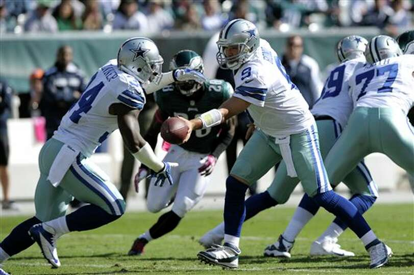 Dallas Cowboys quarterback Tony Romo (9) hands off to running back Phillip Tanner (34) during the fi