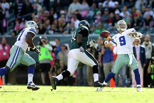 Dallas Cowboys quarterback Tony Romo (9) throws a pass as Philadelphia Eagles defensive end Fletcher Cox, center, chases after Romo during the first half of an NFL football game, Sunday, Oct. 20, 2013, in Philadelphia. Photo: Matt Rourke, AP / AP