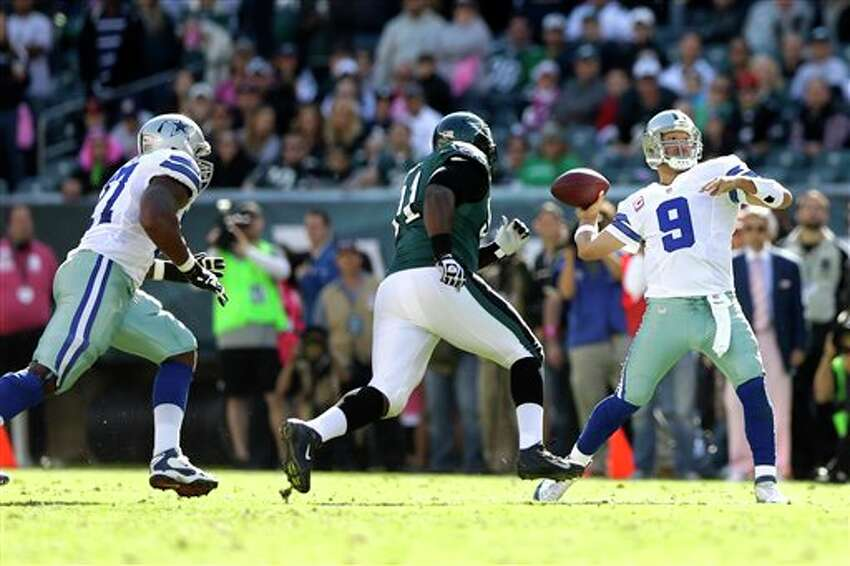 Dallas Cowboys quarterback Tony Romo (9) throws a pass as Philadelphia Eagles defensive end Fletcher Cox, center, chases after Romo during the first half of an NFL football game, Sunday, Oct. 20, 2013, in Philadelphia.