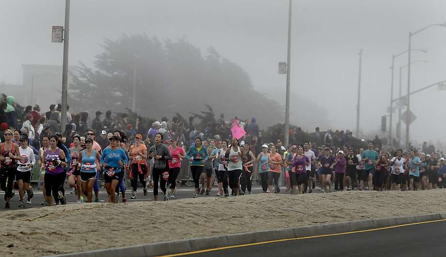 Half marathon runners almost got lost in the fog as they approached the finish line on the Great Highway Sunday October 20, 2013 in San Francisco, Calif. Thousands of women and a few men took part in the annual Nike Women's Marathon which began at Union Square and finished along the Great Highway. Photo: Brant Ward, The Chronicle